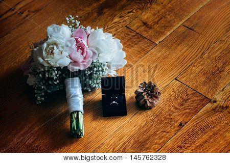 Bridal bouquet of roses, wedding rings in the box and pine cone on a wooden planks