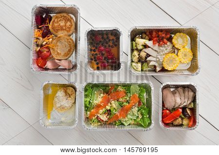 Healthy food delivery, daily ration. Take away of natural organic low carb diet of vegetables and meat. Fitness nutrition in foil boxes. Top view, flat lay with copy space at white wood