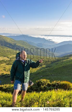 Young man standing on the top of mountain and show finger at far away in sunrise time Carpathians