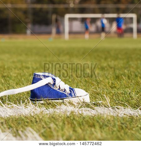 Standing sports shoe on the football field. Sport concept, despair, defeated