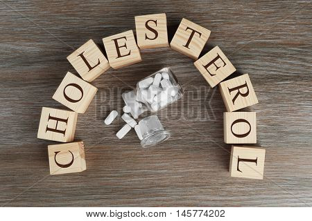 Cubes with word Cholesterol and pills on wooden background