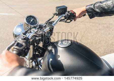 I have passion for open road. Top view of motorcycle and guy sitting on it and keeping handlebar against asphalt road