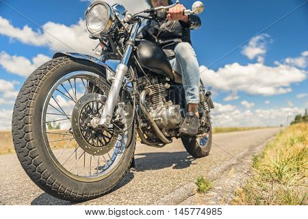 Taking joyride. Cropped shot of biker man on motorcycle against blue sky with white clouds background