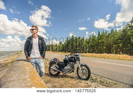 Thinking about open road. Young guy in sunglasses and leather jacket standing along road, looking at lake with his motorcycle in background