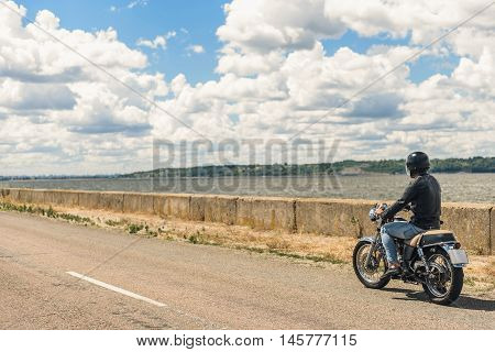 Road is my life. Motorcyclist driving motorcycle along asphalt road near lake in morning sun