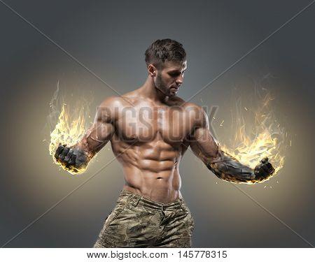Handsome power athletic man bodybuilder. Fitness muscular body on dark background.