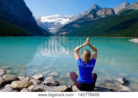 Woman in yoga pose by Lake Louise in Rocky Mountains. Banff National Park. Alberta. Canada.