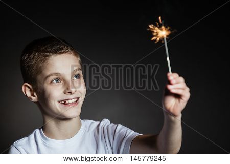 Amazed Boy In White Shirt Holding Sparkler