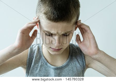 Stressed Young Boy Holding Temples With Hands