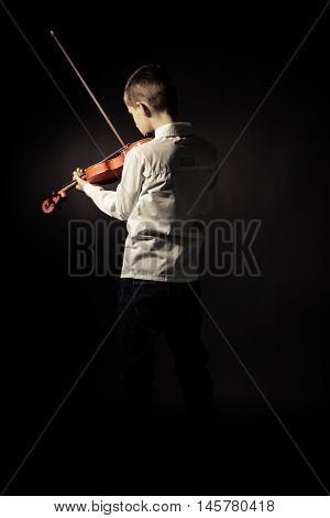 Rear View Of Boy With Violin On Black Background