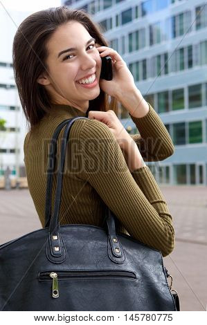Happy Woman With Cellphone Looking Over Shoulder