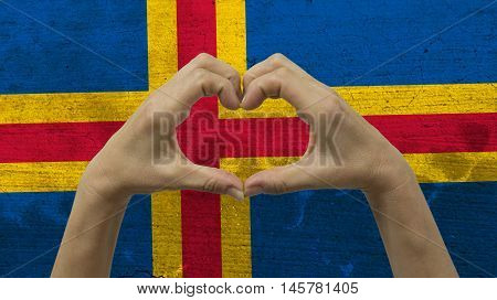 With a stylized Alandic flag background an anonymous person's hands being held in the form of a heart, symbolizing love and patriotism for Aland Islands.