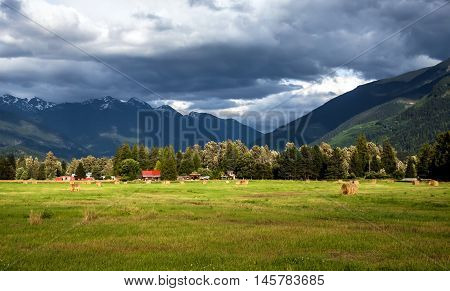 The farm in a mountain valley, hayfield, in the mountains of storm begins