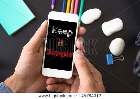 Keep it simple, text message on screen at hands take smartphone, black table with office supplies backdrop background . business concept
