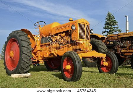ROLLAG, MINNESOTA, Sept 1, 2016: An Minneapolis Moline ZB tractor is parked by hay racks of wheat bundles at the West Central Steam Threshers Reunion(WCSTR) where 1000s attend each Labor Day weekend in Rollag, MN each year.