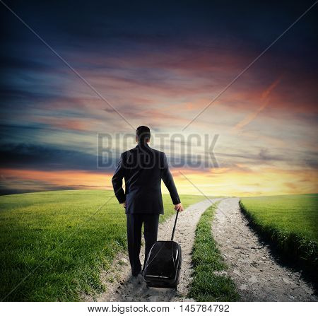 Businessman with luggage walk on road in the countryside with green grass at sunset