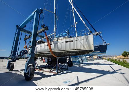 Sailboat pulled ashore by crane in Croatia harbour