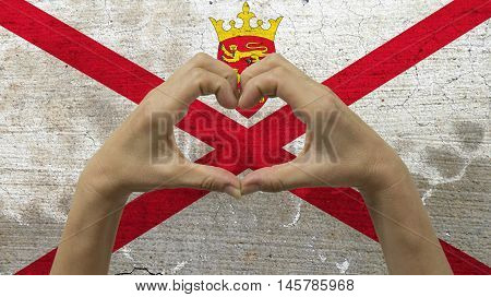With a stylized Jersey flag background an anonymous person's hands being held in the form of a heart symbolizing love and patriotism for Jersey
