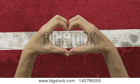 With a stylized Latvian flag background an anonymous person's hands being held in the form of a heart symbolizing love and patriotism for Latvia.
