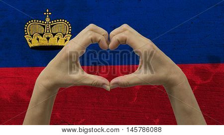 With a stylized Liechtensteinan flag background an anonymous person's hands being held in the form of a heart symbolizing love and patriotism for Liechtenstein.