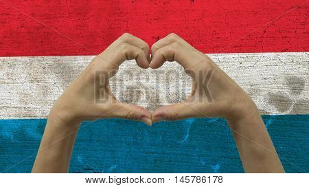 With a stylized Luxembourgish flag background an anonymous person's hands being held in the form of a heart symbolizing love and patriotism for Luxembourg.