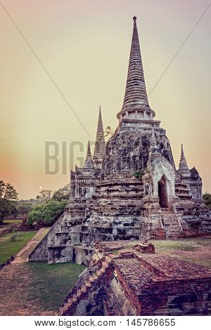 Vintage style add texture effect ancient ruins and pagoda of Wat Phra Si Sanphet old temple famous attractions during sunset at Phra Nakhon Si Ayutthaya Historical Park Ayutthaya Province Thailand