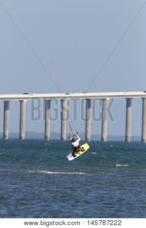 Tampa Bay Florida USA - February 28 2011: Kiteboarder's jump with Sunshine Skyway Bridge in background
