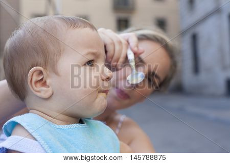 Mother trying to feed her baby boy with fruit mush although he is refusing it