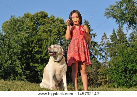 Adorable little girl and her dog outside blowing bubbles
