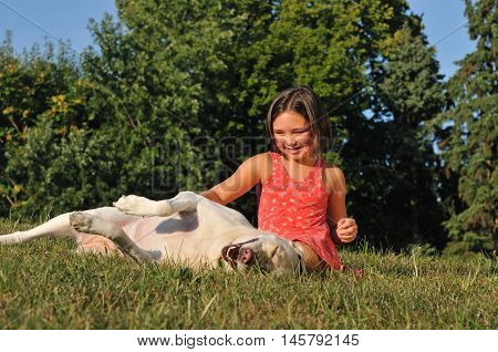 cute little girl having fun playing outside with happy dog