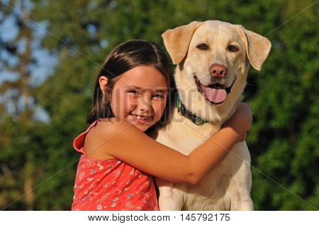 portrait of happy girl hugging her labrador dog outside
