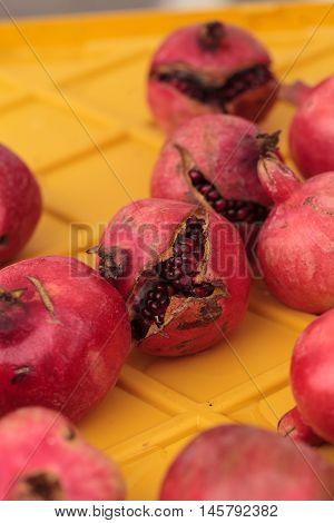 Organic red pomegranates in a bushel of vegetables at a farmers market