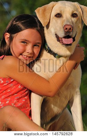 Portrait of adorable little girl hugging her pet dog outside