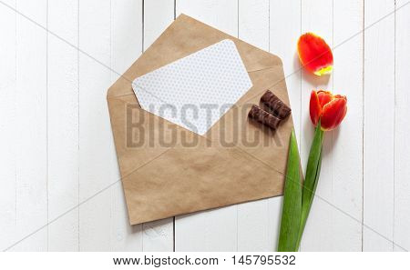 Spring bouquet of red tulips and a card in an envelope on a white wooden background with copy space. View from the top with space for signature.