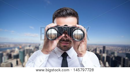 Businessman using binoculars to look at a city
