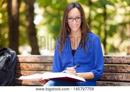 Young woman studying at the park