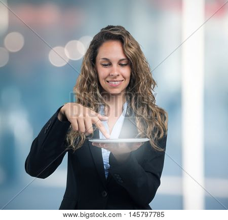 Portrait of a young smiling woman using a digital tablet