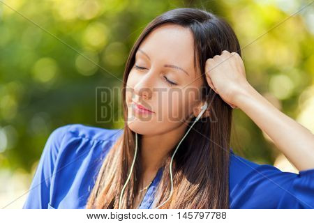 Young woman listening music in a park