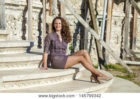 Portrait in full growth, young beautiful brunette woman in brown dress sitting on stone steps