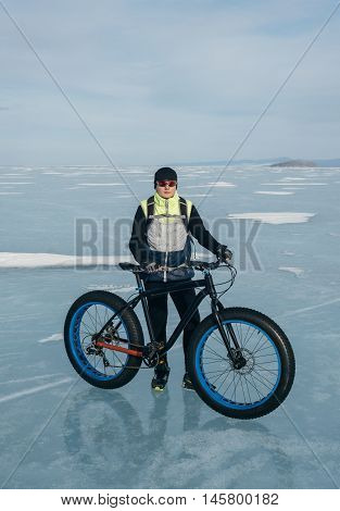 Fatbike (also called fat bike or fat-tire bike) - Cycling on large wheels. Cyclist holding a bicycle looking at the camera. They are standing on the frozen lake.