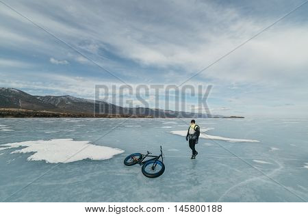 Fatbike (also called fat bike or fat-tire bike) - Cycling on large wheels. Cyclist goes to his bike on the frozen lake.