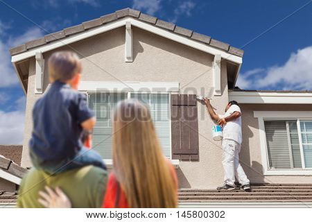 Young Family Watching Home Get Painted by House Painter.