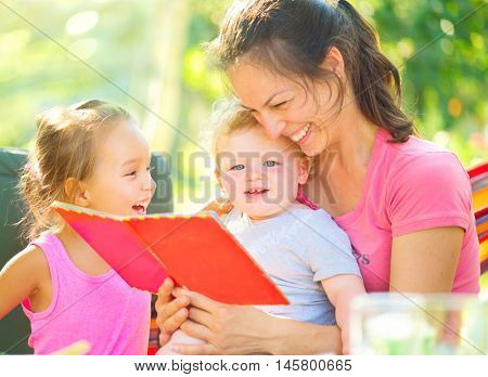Happy mother reading a book to her little babies in sunny park. Joyful young family with children. Mom and kids having fun outdoors in orchard garden, playing together. Laughing and hugging