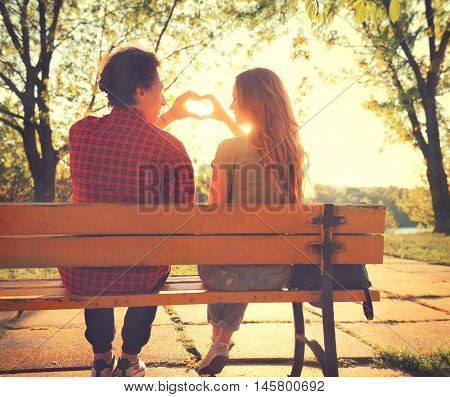 Beautiful happy young couple sitting on the bench in sunny park and making heart gesture together. Girlfriend and boyfriend in love, romantic date