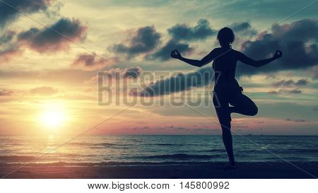 Girl silhouette in yoga pose on the beach by the sea at sunset.