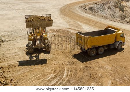 bulldozer working on the open mine loading truck