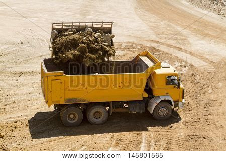 bulldozer working on the open mine loading truck