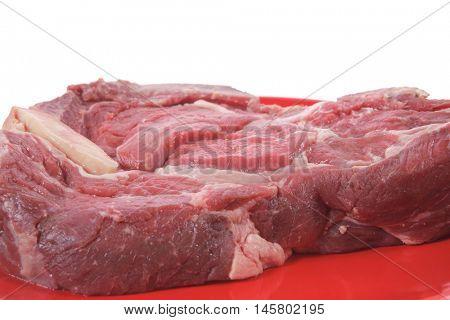 fresh ribeye steak on red plate isolated over white background rib eye
