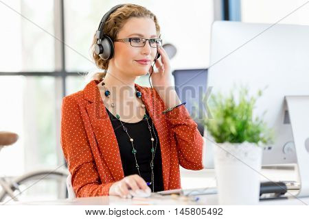 Young woman listening to the music while working on a computer