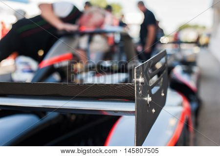 Racing car black rear spoiler detail with out of focus starting grid in background